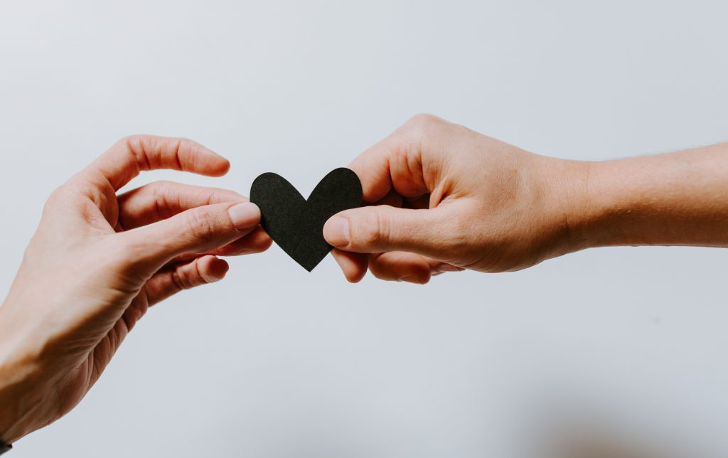Hands holding a paper heart image