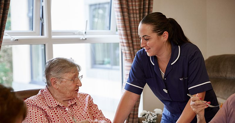 Elderly patient receiving support from a care assistant